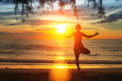 Silhouette young woman practicing yoga on the beach at sunset. Nature. Royalty Free Stock Photos