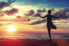 Silhouette young woman practicing yoga on the beach at surrealistic sunset. Royalty Free Stock Photos