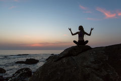Silhouette young woman practicing yoga on the beach at twilight. Royalty Free Stock Photography