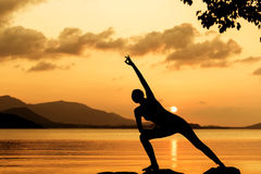 Silhouette young woman practicing yoga Stock Images
