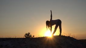 Silhouette young woman practicing yoga and Meditation at sunset.  royalty free stock photos