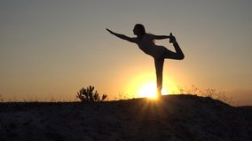 Silhouette young woman practicing yoga and Meditation at sunset.  royalty free stock image