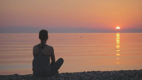 Silhouette of young woman practicing yoga near the sea. Silhouette of young woman practicing yoga on the beach at sunrise stock video
