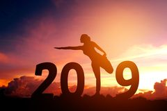 Silhouette young woman practicing yoga on 2019 new year stock photo