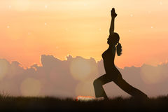 Silhouette young woman practicing yoga Stock Photo