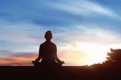 Silhouette of young woman practicing yoga in outdoor Royalty Free Stock Photos