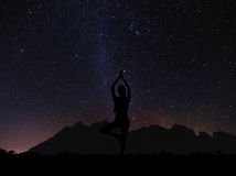 Silhouette young woman practicing yoga pose at night under sky full of stars with colorful milky way Stock Photo