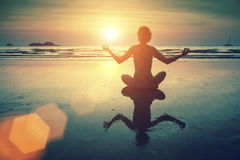 Silhouette young woman practicing yoga on the sea beach at amazing sunset. Relax. Royalty Free Stock Image