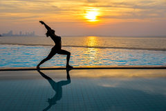 Silhouette young woman practicing yoga on swimming pool and the beach at sunset. Healthy Concept Stock Photos