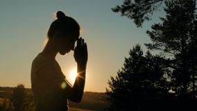 Sporty woman praying in forest at sunset stock video footage