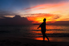 Silhouette of young woman relaxing on the beach at sunset Stock Photos
