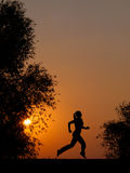 Silhouette of young woman running  Stock Photos
