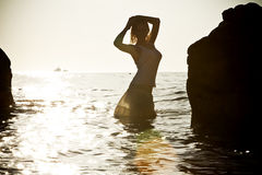 Silhouette of young woman in sea on sunset Royalty Free Stock Photos