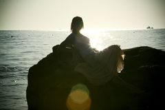 Silhouette of young woman in sea on sunset Stock Photography