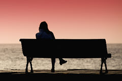 Silhouette of young woman sitting alone on the bench. In front of the sea Stock Image