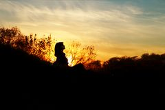 Silhouette of a young woman sitting on a hill at sunset, a girl walking in the autumn in the field royalty free stock photos