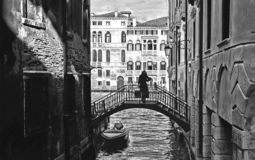 Silhouette of young woman on small old bridge between olden buildings in narrow water canal and facade of historical b royalty free stock images