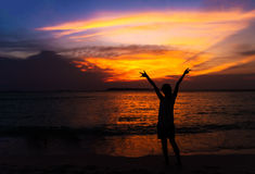 Silhouette of young woman spreading hand and relaxing on the beach Stock Photo