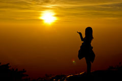 silhouette of Young woman standing arms made a heart shape. Under the Rising Sun stock photo