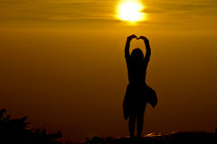 silhouette of Young woman standing arms made a heart shape. Under the Rising Sun royalty free stock image