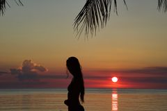 Silhouette of young woman standing on the beach in bikini at su stock photography