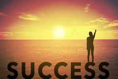 Silhouette young woman standing and raising up her hand about fighting concept on success text over a beautiful sunset or sunrise Stock Photography
