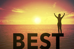 Silhouette young woman standing and raising up her hand about winner concept on BEST text over a beautiful sunset or sunrise Stock Image