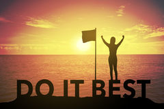 Silhouette young woman standing and raising up her hand about winner concept on DO IT BEST text over a beautiful sunset or sunrise Royalty Free Stock Images