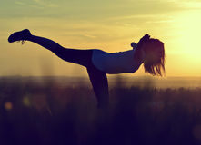 Silhouette of young woman stretching Royalty Free Stock Images