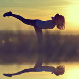 Silhouette of young woman stretching on a meadow Royalty Free Stock Photography