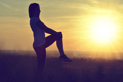 Silhouette of young woman stretching Royalty Free Stock Photos