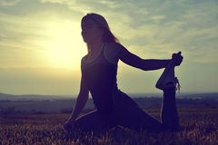Silhouette of young woman stretching on a meadow Stock Photos