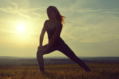 Silhouette of young woman stretching on a meadow Stock Images