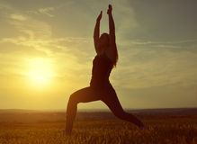 Silhouette of young woman stretching on a meadow Stock Photo