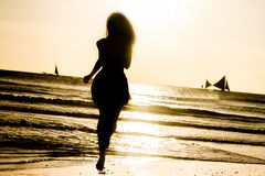 Silhouette of young woman on sunset background Royalty Free Stock Photo
