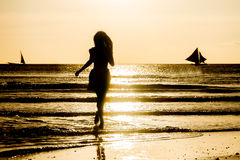 Silhouette of young woman on sunset background Stock Images