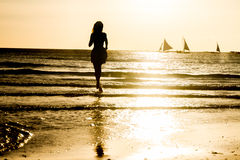 Silhouette of young woman on sunset background Stock Photo