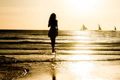 Silhouette of young woman on sunset background Royalty Free Stock Image