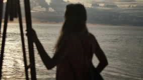 Silhouette of young woman on the sunset. Rear view. Young beautiful woman stands towards the sun on Sea beach during a amazing sunset. Young woman standing on a stock footage