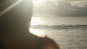 Silhouette of young woman on the sunset. Rear view. Young beautiful woman stands towards the sun on Sea beach during a amazing sunset. Young woman standing on a stock video footage
