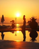 Silhouette of a young woman in the sunset. Young woman standing by the hotel pool and the sea. The wonderful light created some awesome silhouettes and Royalty Free Stock Photo
