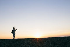 Silhouette of a young woman taking pictures on the camera at sunset Royalty Free Stock Photography