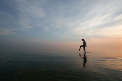 Silhouette of young woman wading in sea. At sunset stock photos