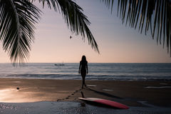 Silhouette of young woman walking aling the beach at sunset Royalty Free Stock Images