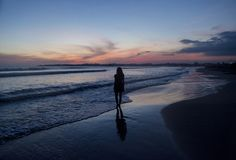 Silhouette of a young woman walking on the beach during sunset time. In Sri Lanka royalty free stock images