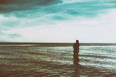Silhouette of young woman walking on sea at sunset Royalty Free Stock Photo