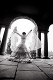 Silhouette of young woman wearing bridal gown in archway. Holding veil Royalty Free Stock Photography