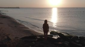 Silhouette of a young woman who is facing sunrise at sea Video shooting from the air Sandy beach with blocks of stone stock footage