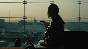 Young woman working with laptop in airport terminal. Waiting for my flight. Silhouette against the background of a large. Silhouette of young woman working with stock video footage