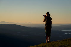 Silhouette of young women taking picture of sunset Stock Photo